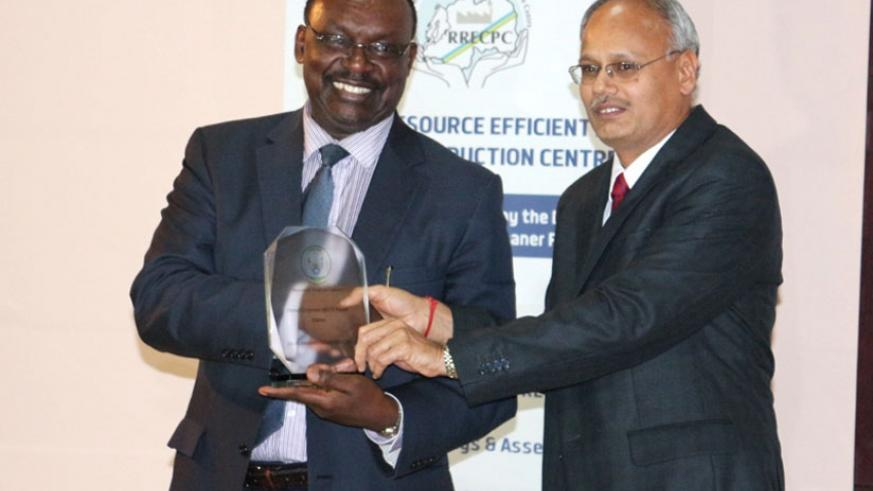 Kanimba (L) presents the overall winner's plaque to  A.S Natarajan, the Sulfo finance manager, on Thursday. (M. Nkurunziza)