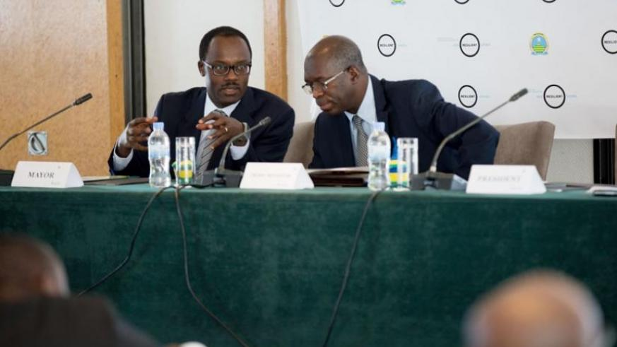 Premier Murekezi (R) consults with Ndayisaba during the workshop in Kigali yesterday. (Timothy Kisambira)
