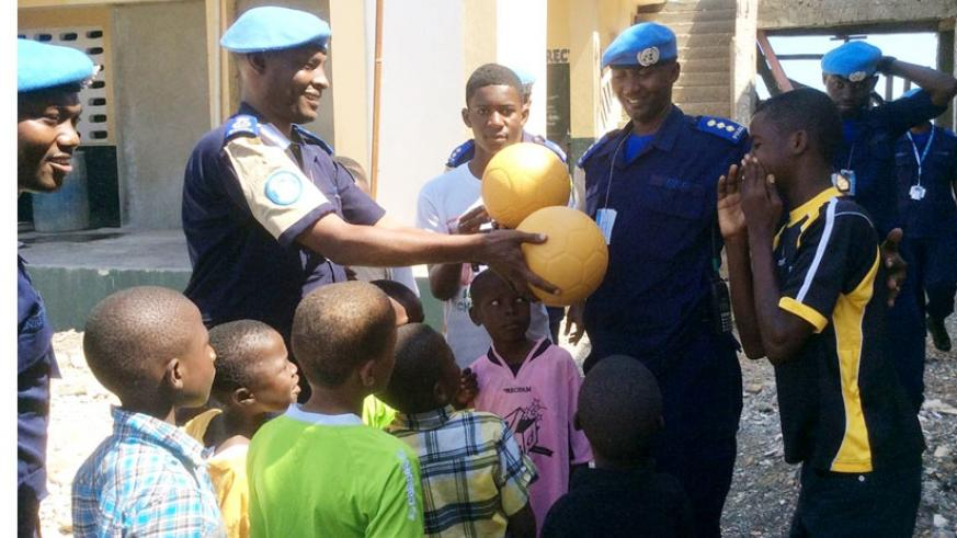 Munyambo hands over balls to an orphan. (Courtesy)