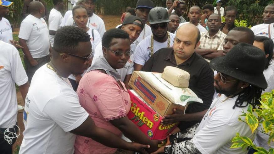 Vipul Kapul and the artistes hand over aid to Clodette Mukamamanzi.