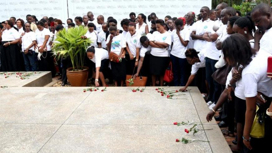 Mourners place roses on a mass grave at Kigali Genocide Memorial Centre, Gisozi, last week, in honour of the victims of the 1994 Genocide against Tutsi. (John Mbanda)