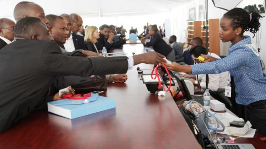 Delegates pick their accreditation cards before a series of AFDB meetings in Kigali last year. (File)