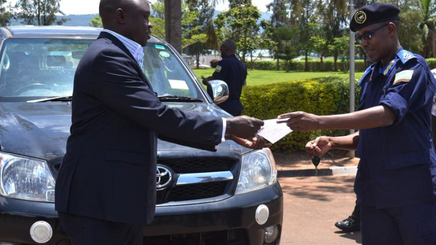 Commissioner for Interpol, ACP Tony Kuramba (R) hands over a stolen Toyota Hilux pickup truck recovered in Rwanda, to Patrick Lawot, the Liaison Officer at the Uganda High Commission in Rwanda. (File)
