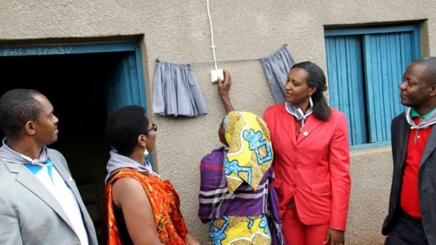 Mukamusigwa turns on a switch after her home was connected to electricity. (Michel Nkurunziza)