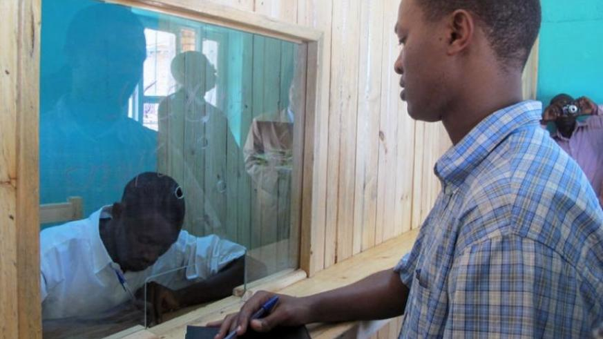 A client waits to receive money from a teller at a Credit Savings Cooperative (SACCO). (John Mbanda)