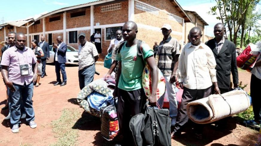 Some of the ex-M23 fighters leave to board the minibus to return to DR Congo. (John Mbanda)