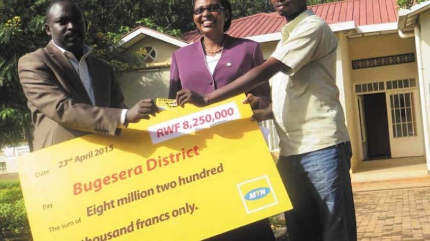 ETO deputy head teacher in charge of discipline, Gasana Etienne (right), at receives a mobile money-enabled SIM card from Rwagaju and Asiimwe at the district head offices. The students' fees will be sent using mobile money transfer service. (Jean Nepo Ndikumana)