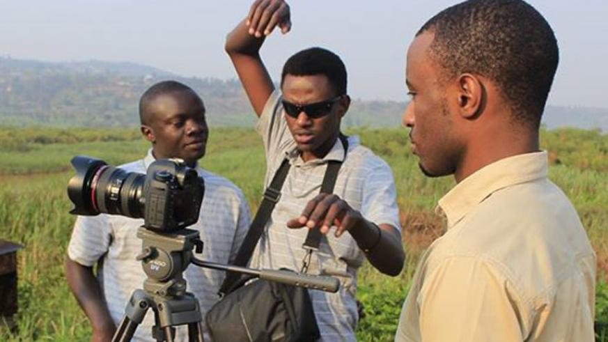 Philbert Aime Mbabazi (middle) and his crew on a set during a shooting session. (Courtesy).