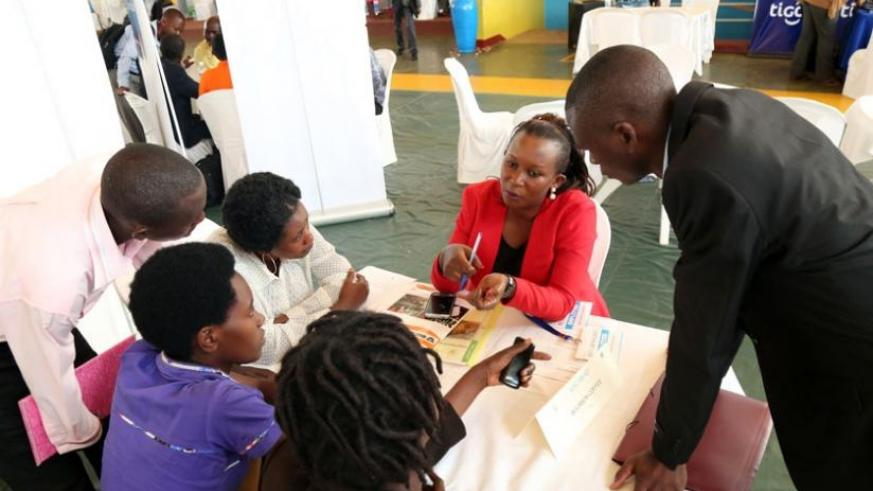 Job-seekers speak with a potential employer at the job fair in Remera on Tuesday. (John Mbanda)