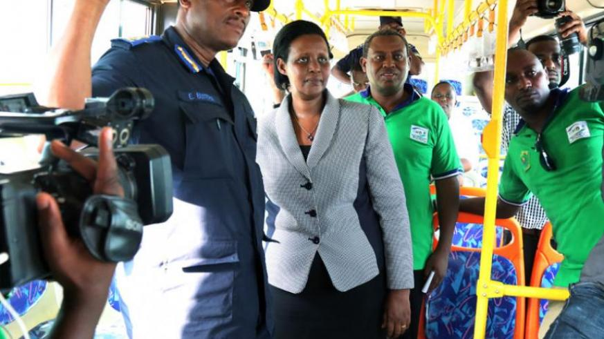 Gender Minister Oda Gasinzigwa (C) with Commissioner of Police Emmanuel Butera (L) and KBS Chairman Charles Ngarambe watch an onboard video message in a bus yesterday. (John Mbanda)