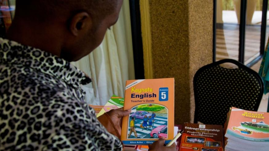 A reader checks out one of the books published by Longhorn Publishers. (Doreen Umutesi)