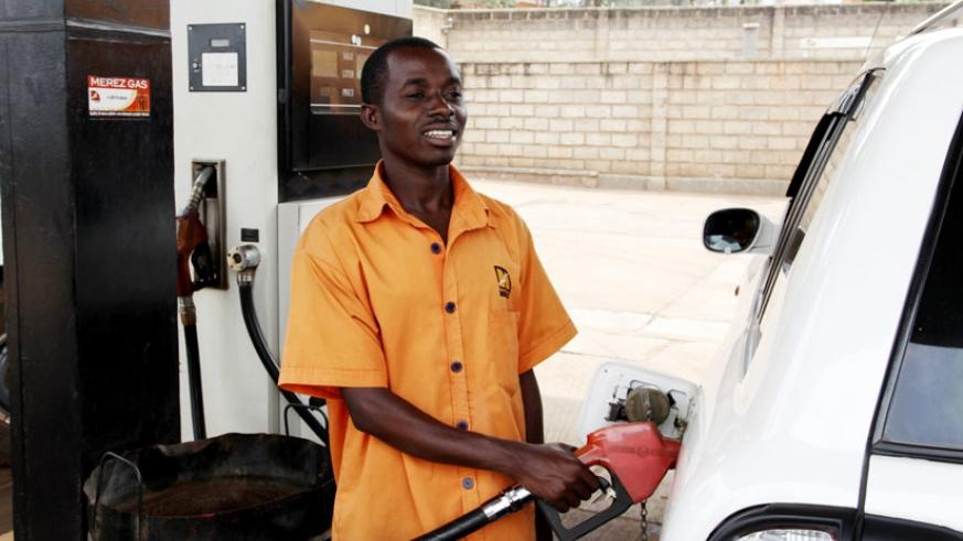 A pump attendant refills a car. Fuel pump prices are rising again after plummeting for months. (File)