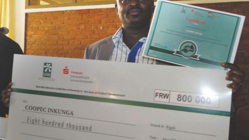 Nsengimana displays a dummy cheque for COOPEC Inkunga Sacco worth Rwf0.8m. The Sacco won in the ICT innovation category. (Peterson Tumwebaze)