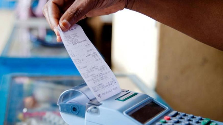 A trader pulls a receipt out of an e-Billing machine. Electronic billing was introduced to curb tax evasion and boost revenue collection. (File)