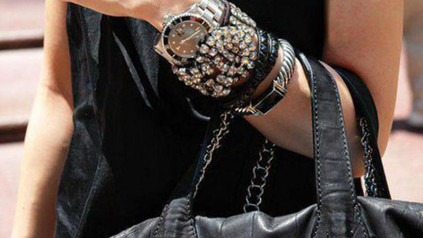 A trendy watch, wrist bands and bag.