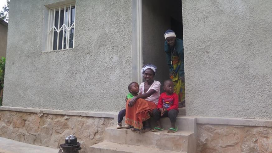 Family of Therese Umwanayezu sit in front of their newly renovated home. (Frederic Byumvuhore)