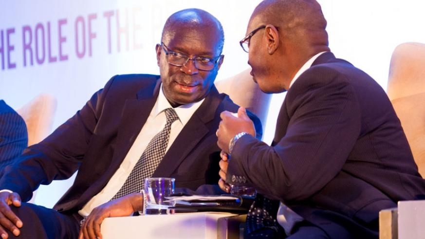 Prime Minister Anastase Murekezi (L) chats with the State minister for Public Health and Primary Health Care, Dr Patrick Ndimubanzi, at the fourth conference of the East Africa Healthcare Federation in Kigali yesterday. (All photos by T. Kisambira)