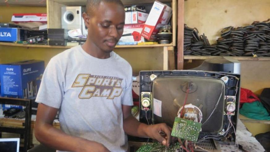 A technician repairs a TV set. Most businesses are not aware that they can use their good credit history to get lower loan rates. (Jean Nepo Ndikumana)