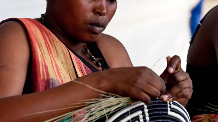 A woman weaving a basket. These are some of the products that Rwanda exports to the US. (Timothy Kisambira)