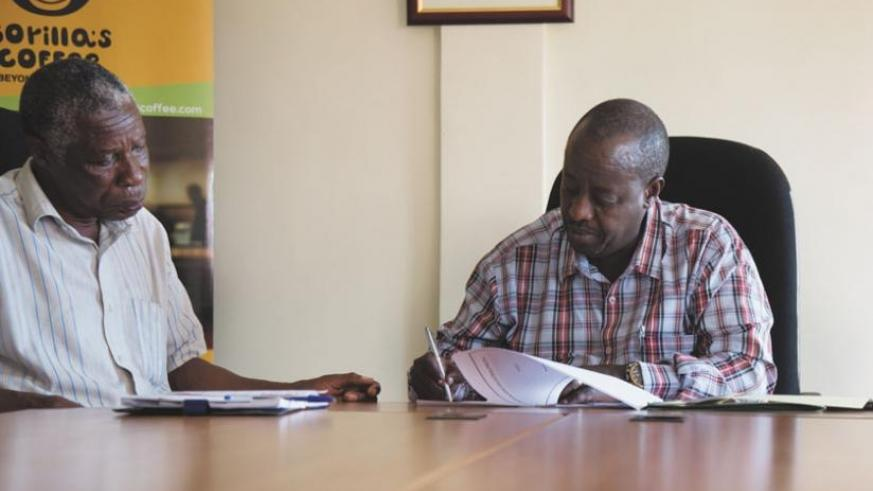 Uwimana (right) signs the funding agreement at NAEB head offices on Tuesday as Dukundekawa-Musasa Co-operative's Minani (left) looks on. (Timothy Kisambira)