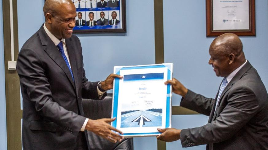 RwandAir CEO John Mirenge (L) receives a certificate from Raphael Kuuchi, the vice president of International Air Transport Association at Kigali International Airport yesterday. (All photos by Timothy Kisambira)