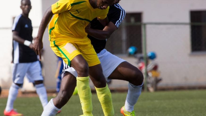 AS Kigali's Justin Mico (in yellow) fights for the ball with Yannick Mukunzi of APR in a league encounter in March. (File)