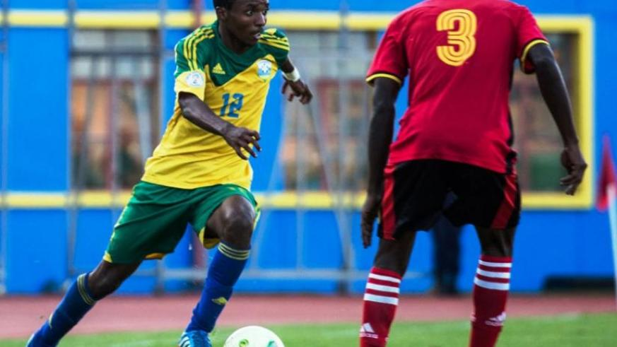 Dominique Savio Nshuti  (L) attempts to go past a Ugandan defender during the Olympic qualifier first leg in Kigali recently. (T. Kisambira)