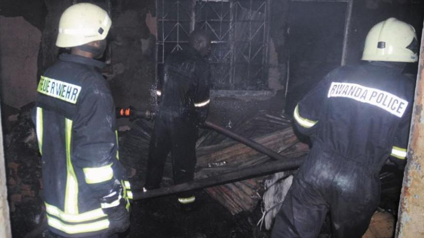 Policemen put out fire that engulfed stores in Kigali last year. Insurance reduces burden of such fires. (File)