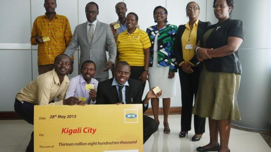 City of Kigali mayor Fidele Ndayisaba (second left, standing) poses for a picture with beneficiary school heads and MTN Rwanda officials. (Courtesy)