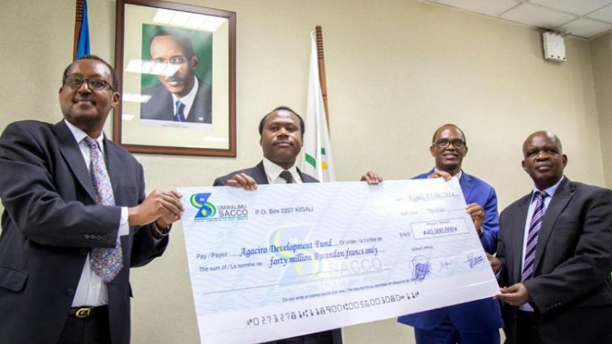 L-R; Kagabo, Dr Ndagijimana, Joseph Museruka, the managing director of Umwalimu SACCO, and Nzagahimana pose with the dummy cheque during the handover of the donation yesterday. (Timothy Kisambira)