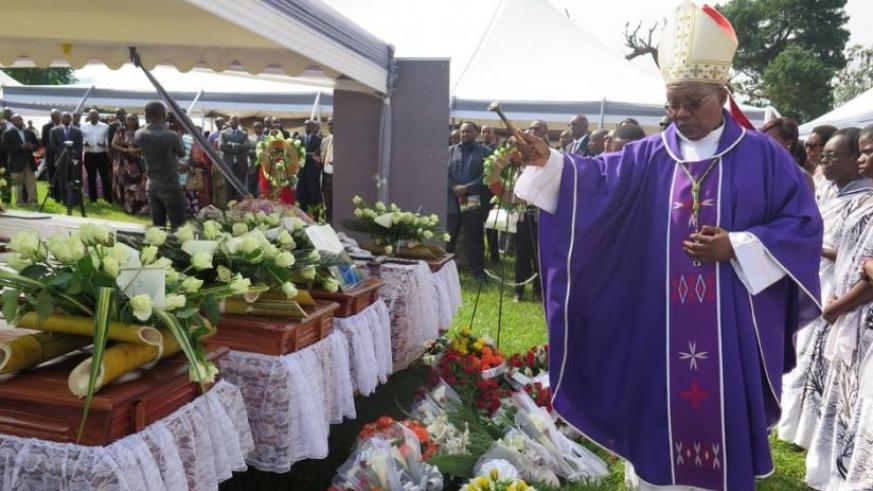 Monsignor Philip Rukamba, the Bishop of Butare Cathedral, sprinkles holy water on caskets containing the remains of some of the Genocide victims before their burial on Sunday.  (Emmanuel Ntirenganya)