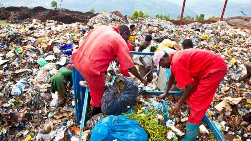 Workers at Nduba Dump Site in Gasabo District sort garbage. (Timothy Kisambira)