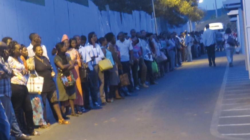Passengers wait for Kimironko buses at 7pm at a downtown bus terminal last week.The first person and the last on the queue boarded buses at the same time as five buses thronged terminal within seconds of each others.  (Jean Mugabo)