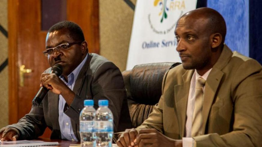 (L-R) The Permanent Secretary of the Ministry of Local Government Vincent Munyeshyaka speaks at the launch of Rwanda Automated Local Government Taxes Management Systems while Richard Tushabe, Rwanda Revenue Authority Commissioner General, looks on. (Doreen Umutesi)