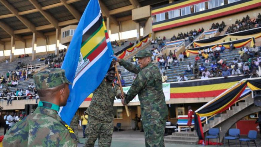 RDF Chief of Defence Staff, Gen Patrick Nyamvumba, receives the EAC flag from his Ugandan counterpart Gen Edward Katumba Wamala (L) at Namboole Stadium in Kampala, yesterday, signifying hand over of hosting rights to Rwanda for the next EAC Military Games edition due 2016. (Courtesy)