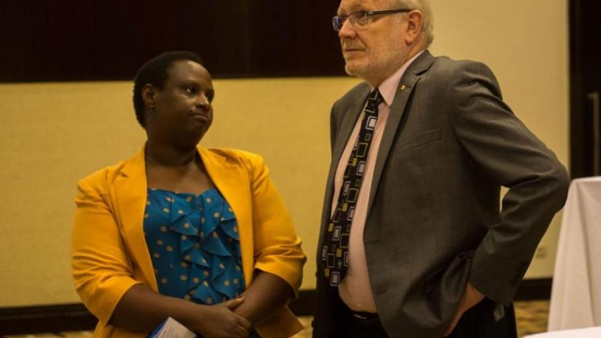 Dr Usta Kayitesi, the principal of the University of Rwanda's College of Arts and Social Sciences (L), chats with Prof James McWha, the vice-chancellor of the University of Rwanda. (Timothy Kisambira)