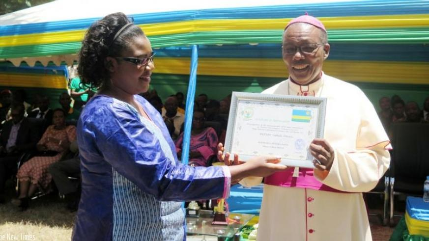 The Minister for Public Service and Labour, Judith Uwizeye, hands over an award of recognition by Huye District to the Bishop of Butare Catholic Diocese Monsignor Philip Rukamba on Tuesday. (Timothy Kisambira)