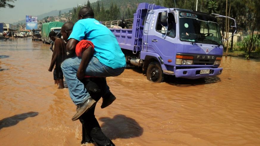 A man is carried across the flooded Nyabugogo road. EALA members want partner states to promote awareness campaigns in order to reduce vulnerability. (File)