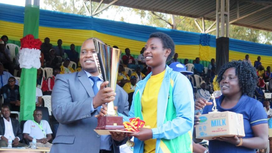 State Minister for  Education Olivier Rwamukwaya (L) hands over the volleyball trophy to Inderabarezi captain  Jacqueline Uwamariya. (E. Ntirenganya)