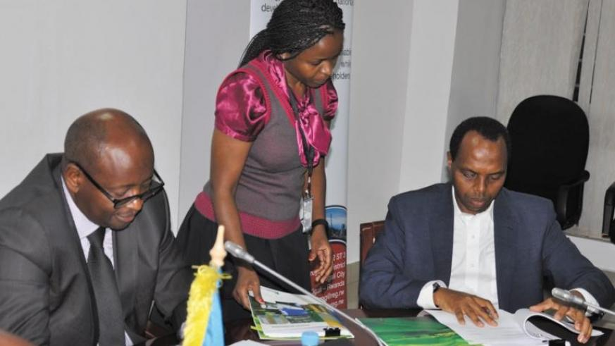 RDB's Francis Gatare signs the lease deals as Minister Musoni looks on. (P. Tumwebaze)