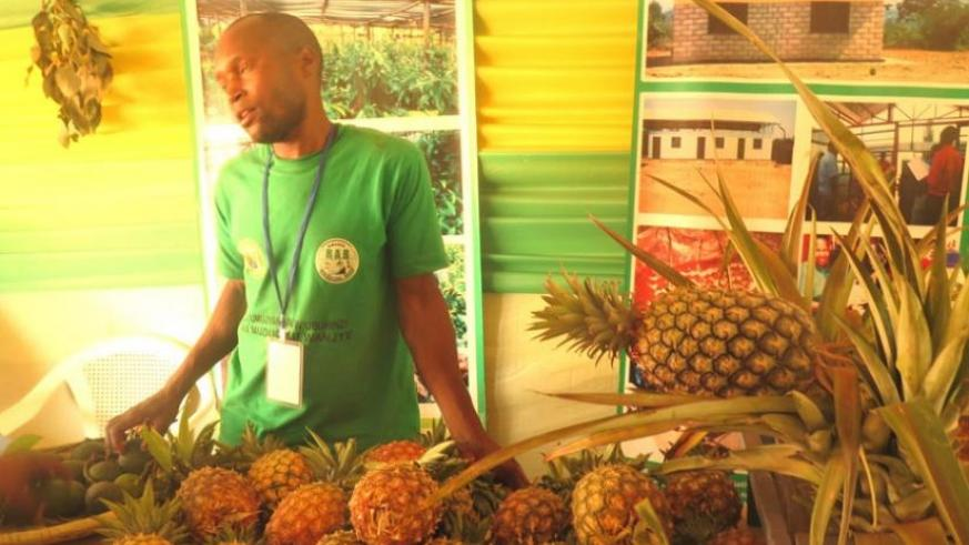 A pineapple farmer showcases his produce at the trade fair. (Stephen Rwembeho)