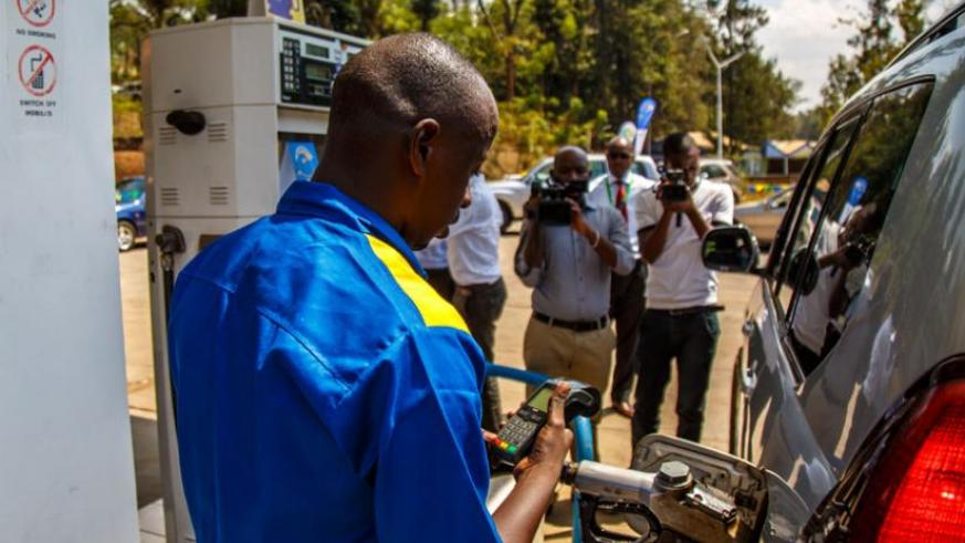 Remy Rugayabahunga, a fuel pump attendant with SP Rugunga service station in Kigali, refills a vehicle as he bills using electronic visa billing machine during the launch of the card-based electronic payment yesterday. (Timothy Kisambira)