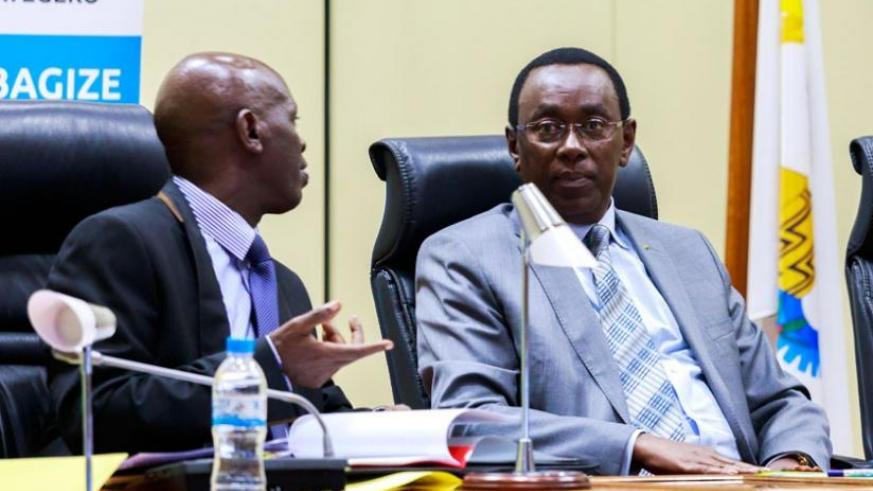 MP Theoneste Karenzi (L) chats with Makuza during the General Assembly of the Parliamentary Forum against Genocide  (T.Kisambira)