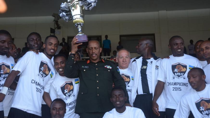 Gen, Patrick Nyamvumba, Chief of Defence Staff of the Rwandan Defence Forces (C) holds the trophy after APR were crowned league champions last season. (S. Ngendahimana)