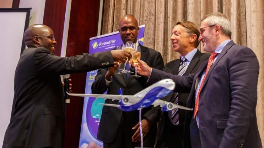 (L-R) Dr Alexis Nzahabwanimana, the State Minister for Transport; John Mirenge, the chief executive officer of RwandAir; Christopher Buckley, the Airbus's executive vice-president Africa, Europe and Asia Pacific; and Kevin Evans, the Rolls Royce vice-president - customers, toast to the deal at the signing ceremony in Kigali yesterday. (Timothy Kisambira)