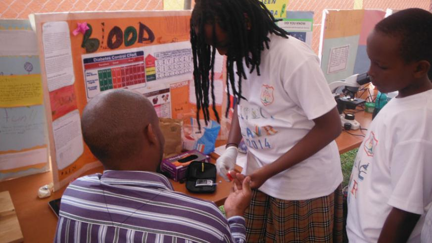 A student of Hope Academy takes a blood sample from one of the parents as another one  (right) examines the sample using a microscope.