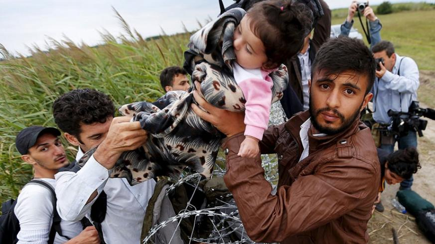 A Syrian migrant hands a girl to another migrant over the barbed wire barrier along the Hungarian-Serbian border. (Courtesy)