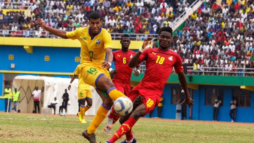 Amavubi forward Rushenguziminega attempts to shoot as the Ghana defender blocks at Amahoro pitch which observers say was in a poor state last Saturday. (T. Kisambira)