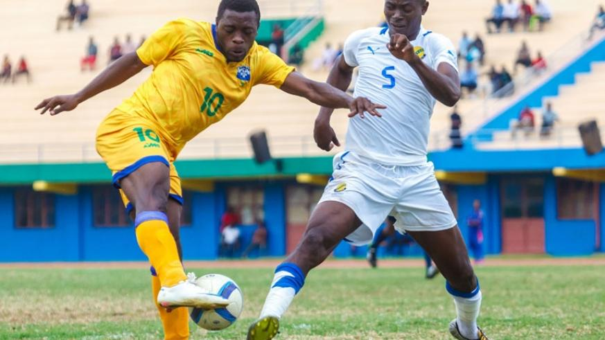Amavubi debutant Songa (L), tries attempt on goal which is blocked by a Gabonese defender on Saturday. (Timothy Kisambira)