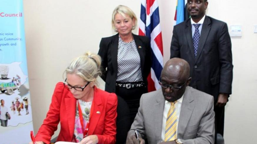 Traaseth (L) and Karera sign the paperwork in a ceremony witnessed by Maeland, and Sezibera (standing right) in Arusha, Tanzania, yesterday. (Courtesy)